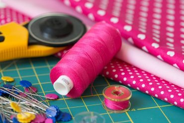 Image of sewing tools and materials - cotton reel, materials and pins