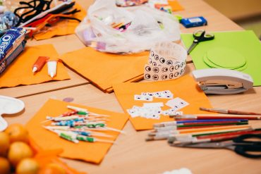 Arts and crafts materials laid out over a table - paper, pencils, stickers, scissors