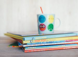 A children's drinking cup with a straw on top of a pile of children's books